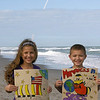 Andrea (age 10) and Jake (age 8) show off their Monarchs in Space art on location from the Space Coast near Melbourne, FL as the Space Shuttle Atlantis streaks across the sky in the background. Very cool! Photo submitted by Cheryl M.